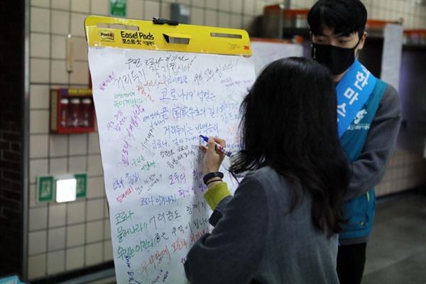 한 시민이 코로나19 극복을 위한 응원 메시지를 남기고 있다 .