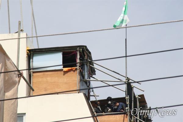 대구 중구 동인3-1지구 재개발사업이 진행중인 가운데 조합이 강제집행에 들어가려 하자 철거민들이 건물 옥상에 마련된 망루에 올라가 병을 던지며 저항하고 있다.