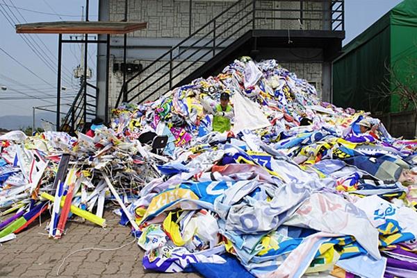 춘천시의 위탁을 받아 폐현수막으로 쓰레기 분리수거용 마대자루를 만드는 춘천시니어클럽 작업장 마당에 폐현수막이 산처럼 쌓여 있다.