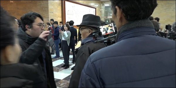 2019년 12월 13일 국회 로텐더홀에서 진보 성향 유튜브 채널 <서울의 소리>백은종 대표와 설전을 벌이고 있는 박창훈씨. 손에는 유튜브 방송을 위해 스마트폰을 들고 있다.