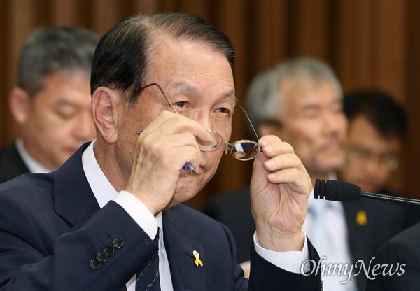 2014년 7월 10일 김기춘 대통령 비서실장이 국회에서 열린 세월호 침몰사고 진상규명을 위한 국정조사 특별위원회 기관보고에 출석해 답변도중 안경을 고쳐쓰고 있다.