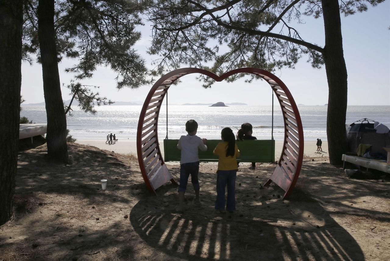부모와 함께 자은도 백길해변을 찾은 어린이들이 그네를 타고 밀어주며 즐거운 시간을 보내고 있다. 지난 3월 29일 오후다.