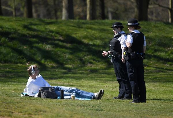 영국 경찰이 5일(현지시간) 런던 그리니치 공원에서 일광욕하는 시민에게 신종 코로나바이러스 감염증(코로나19) 확산 방지를 위한 이동제한령에 따라 귀가할 것을 지시하고 있다. 맷 핸콕 보건장관은 시민들이 이동제한령을 계속 무시할 경우 야외활동을 금지할 수 있다고 경고했다.