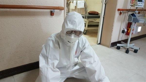 방호복을 입은 의료진이 지쳐서 쉬고 있다.