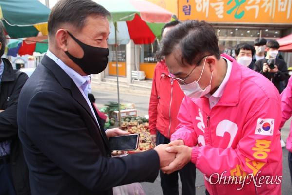 지난 6일 대구 달서구 이곡동 월요시장에서 홍석준 미래통합당 후보가 유권자들을 만나 손을 잡고 인사를 하고 있는 모습.