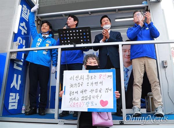 21대 총선 경기도 용인시정 더불어민주당 이탄희 후보가 9일 오후 용인시 보정동 누리에뜰 사거리에서 유세를 하는 가운데, 이 후보 장모가 피켓을 들고 무대차앞에 서 있다.