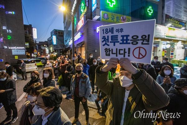 종로에 출마하는 더불어민주당 이낙연 후보가 13일 오후 서울 종로구 평창동에서 집중유세를 하자 일부 지지자들이18세 투표자들을 격려하는 피켓을 들고 있다.
