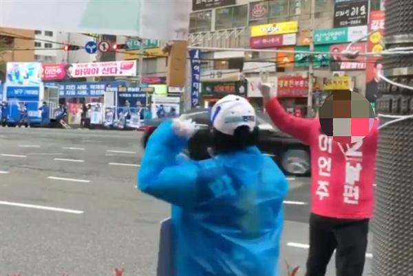 부산 남구을 더불어민주당 박재호 후보 측이 공개한 영상 캡쳐. 미래통합당 이언주 후보의 배우자가 지난 12일 민주당 선거운동원 앞에서 기호 2를 들어보이며 왔다갔다 하고 있다.