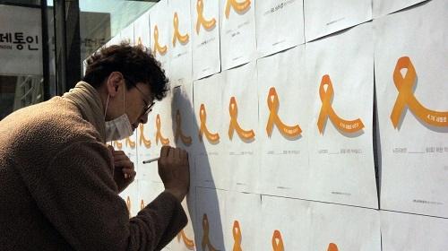 참여연대 상근자가 노란리본약속의 벽에 글을 쓰고 있습니다
