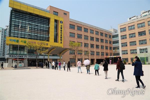 길어진 총선 투표 행렬 21대 총선 투표일인 15일 오전 서울 성북구 숭인초등학교에서 '코로나19' 감염예방을 위해 마스크를 쓴 유권자들이 투표를 하기 위해 운동장에 길게 줄을 서 있다.