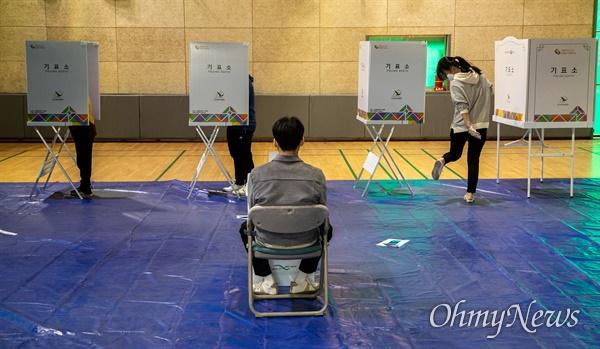 제 21대 총선 투표일인 15일 오전 서울 서대문구 홍제배드민턴장에 마련된 홍제 제3동 제3투표소에서 시민들이 마스크를 쓰고  투표를 하고 있다.