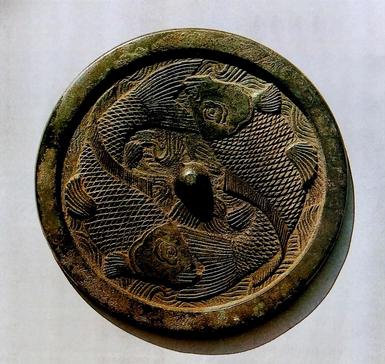 도4 붕어무늬 청동거울 고려. 지름 19.4cm. 북한 개성시 판문군 진봉리. 중국 금나라(1115-1234)에도 물고기 청동거울이 꽤 있다. 이것을 '金代雙魚鏡(금대쌍어경)'이라 한다. 중국과 한국 고고학에서는 이 거울 속 물고기를 보통 다산이나 자식복으로 본다. 하지만 알은 개구리도 많이 낳는다. 그래서 물고기가 왜 청동거울 속에 있는가, 하는 점을 청동거울 역사와 무늬 맥락에서 보아야 한다. 이에 대해서는 청동기미술사에서 자세히 다루겠다. 일단 여기서도, 물고기는 물고기가 아니다.