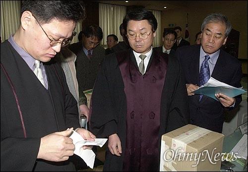 16대 대선 재검표 현장 모습. 사진은 2003년 1월 27일 서울 마포 소재 서울지법 서부지원 10층에서 은평구 유권자들의 재검표가 실시되고 있는 모습이다. 법복을 입은 법관이 투표용지를 확인하고 있는 모습을 이 지역출신 당시 한나라당 이재오 의원(오른쪽)이 지켜보고 있다.