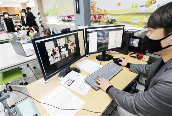 20일 오전 청주시 상당구 낭성초등학교에서 열린 '온라인 입학식'에서 교사가 학생들과 인사하고 있다.