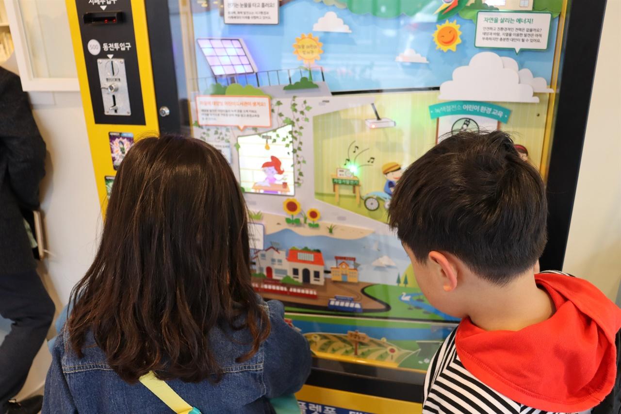 에너지 자판기를 이용하는 어린이들