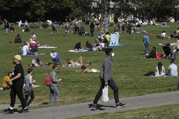 코로나19에도 공원 나온 미국 샌프란시스코 시민들 미국 캘리포니아 주 샌프란시스코의 한 공원에서 3일(현지시간) 코로나19 사태 속 휴식을 취하는 시민들 옆으로 마스크를 쓴 남성이 지나고 있다.