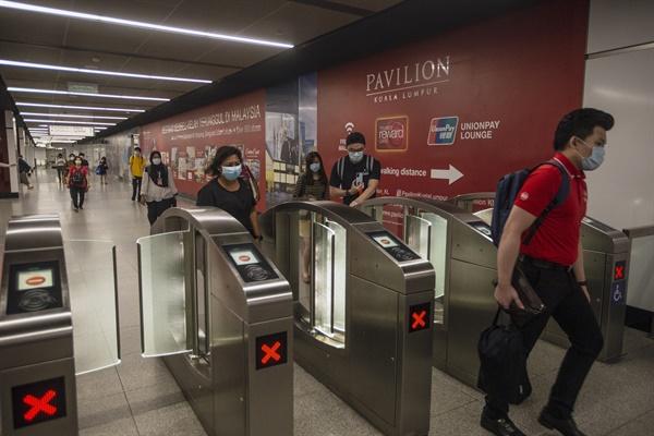 코로나19 봉쇄령 완화된 말레이시아 지하철역 말레이시아 쿠알라룸푸르 지하철역 이용객들이 4일 개찰구를 지나는 모습. 말레이시아 정부는 이날부터 신종 코로나바이러스 감염증(코로나19) 확산 방지를 위한 봉쇄령을 상당 부분 완화하기로 했다.
