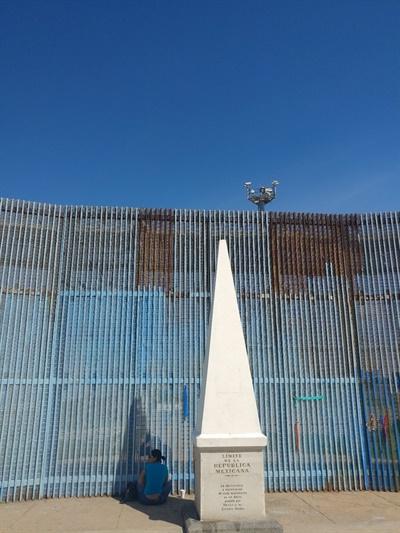 멕시코 영토의 최북단임을 알리는 기념비가 있는 곳에서 한 여성이 국경을 사이에 두고 그 너머 가족 혹은 지인과 대화하고 있다. 국경 철조망 위쪽에 미국측 감시 카메라가 보인다.