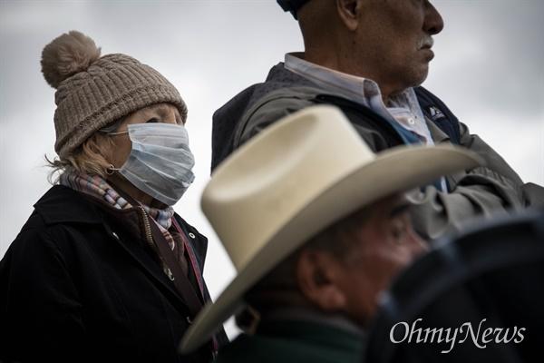 지난 3월 20일 멕시코 띠후아나의 여행자들이 미국 국경을 건너가기 위해 기다리고 있다. 이날 트럼프 대통령은 코로나 바이러스 확산으로 인한 미국-멕시코 국경 폐쇄를 발표했다.