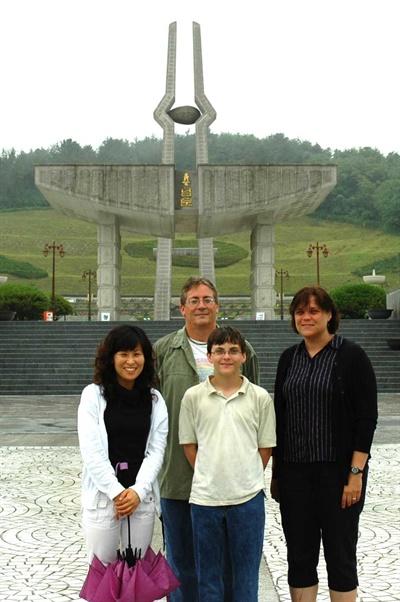 영암에서 평화봉사단으로 근무했던 데이비드 돌린저는 1980년 5.18민주화운동 당시 광주에서의 참상을 목격했다. 사진은 2005년 가족과 함께 한국을 찾은 데이비드 돌린저가 5.18재단 직원과 함께 국립5.18민주묘지에서 찍은 것이다.