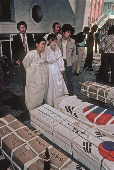 폴 코트라이트의 회고록 <5.18 푸른 눈의 증인>에 실린 로빈 모이어의 사진. 폴은 1980년 5.18민주화운동 당시 <타임> 사진기자였던 로빈의 취재를 도왔다. 소복을 입은 여성이 가족의 관을 가져가기 위해 시신 보관소를 찾아 눈물을 흘리고 있다.