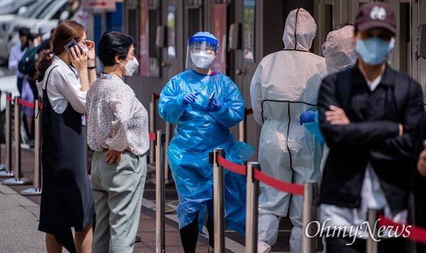 이태원 한  클럽에서 코로나19 확진자가 다녀가 확진자  증가하자 11일 오후 서울 용산구 이태원 인근 대형병원에서 코로나19 검사를 받기 위해 줄을 선 대기자들 사이에서 의료진이 검사 안내를 하고 있다.