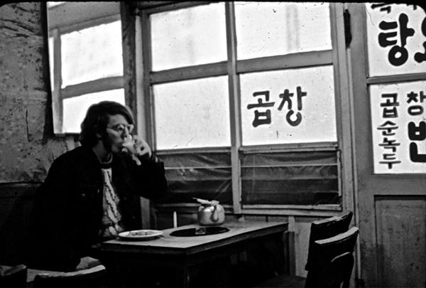평화봉사단 자격으로 1971년~1974년 광주에 머물렀던 도널드 베이커의 모습이 담긴 사진. 1972년 '곱창'이라고 적힌 가게에서 막걸리를 마시고 있는 모습이다.
