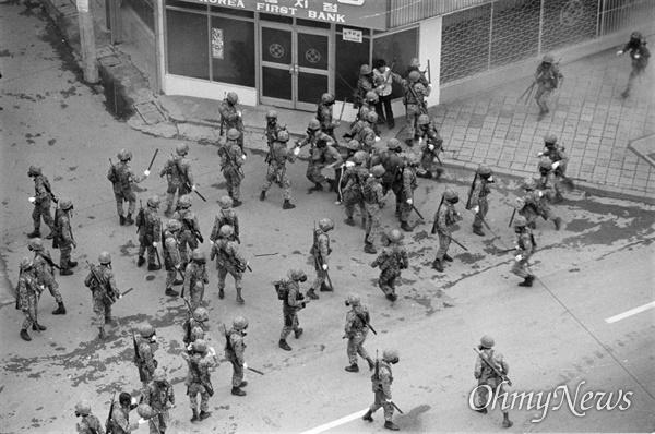 5.18민주화 운동 당시 광주 제일은행(현재 무등빌딩) 앞에서 최루탄이 터진 상황에서 한 시민이 방독면을 쓴 계엄군에 둘러 싸여 겁에 질린 모습을 하고 있다.