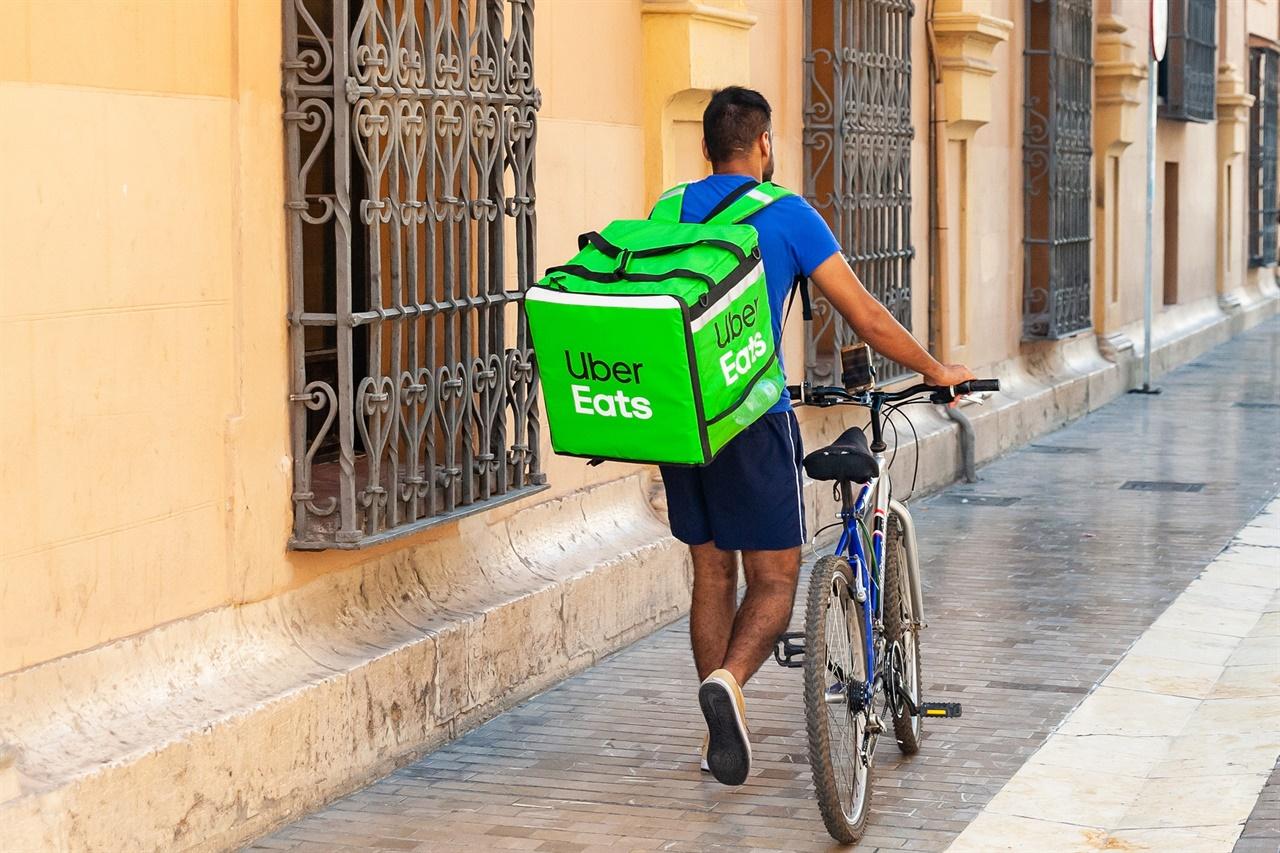 자전거로 음식을 배달하는 우버이츠 배달원.