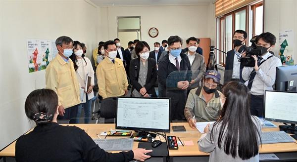 김현수(하늘색 마스크를 쓴) 농식품부 장관이 부여군 공익직불제 접수 현장에서 한 신청자의 공익직불제 신청 과정을 보고 있다.