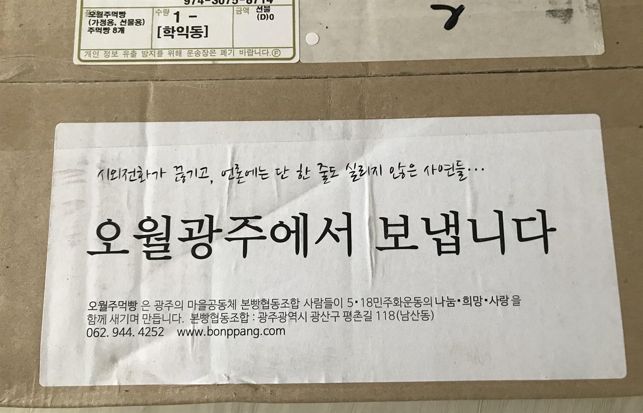 """택배상자에 붙은 스티커. """"오월광주에서 보냅니다"""""""