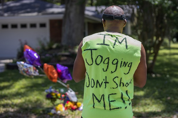 """백인 총격에 숨진 흑인청년 추모하는 미국 남성 지난 5월 8일 미국 조지아주 브런즈윅에서 조깅하다 숨진 흑인 청년 아흐마우드 엘버리를 추모하기 위해 사람들이 모여있다. 한 시민이 """"저는 조깅 중입니다, 쏘지 마세요""""라고 쓰여진 티셔츠를 입고 있다."""