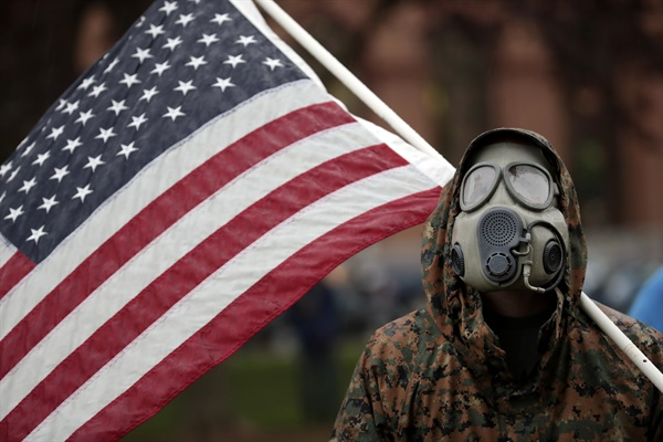 '자택 대피 명령' 항의하는 미국 미시간 주민 14일(현지시간) 코로나19에 따른 미국 미시간 주의 자택 대피 명령에 항의하는 집회에서 한 주민이 방독면을 쓴 채 국기를 들고 있다.