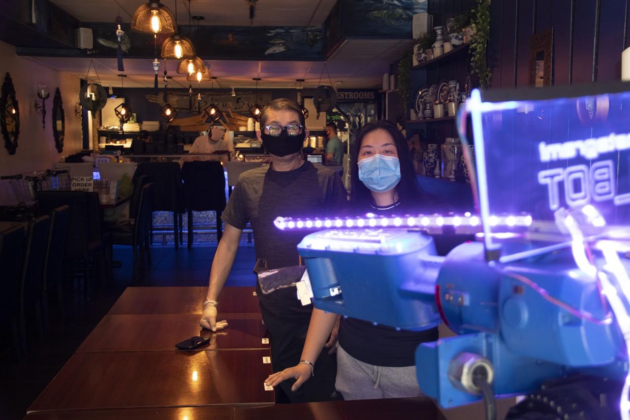 로봇과 함께 일하는 것이 새로운 일상이 된 초밥집   로봇 앞에서 식당 고객서비스를 하고 있는 헨드라 용(Hendra Yong) 블루 스시 사장 부녀.