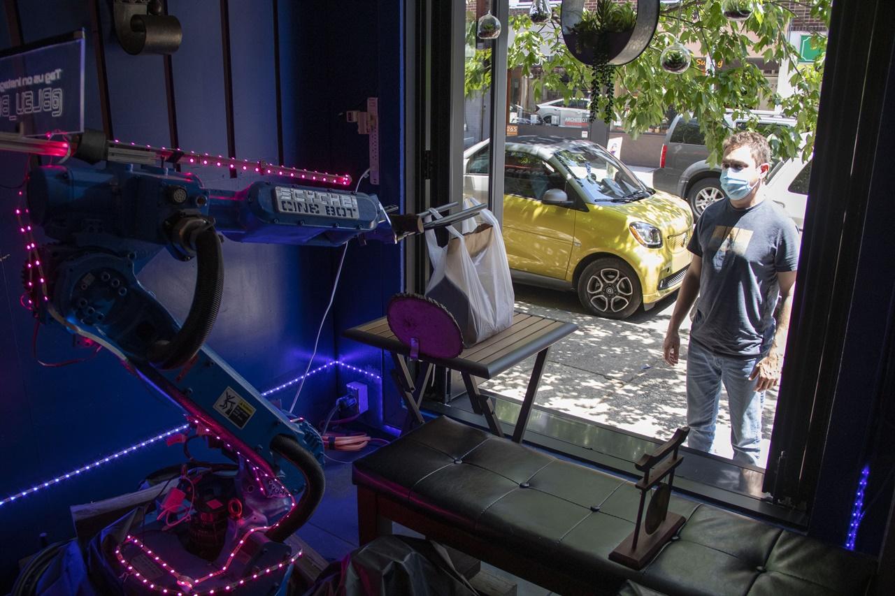 미국 식당 비대면 서비스 로봇 등장 로봇이 식당 창문 밖에서 주문음식 픽업을 기다리는 고객에 포장음식을 전달하고 있다.