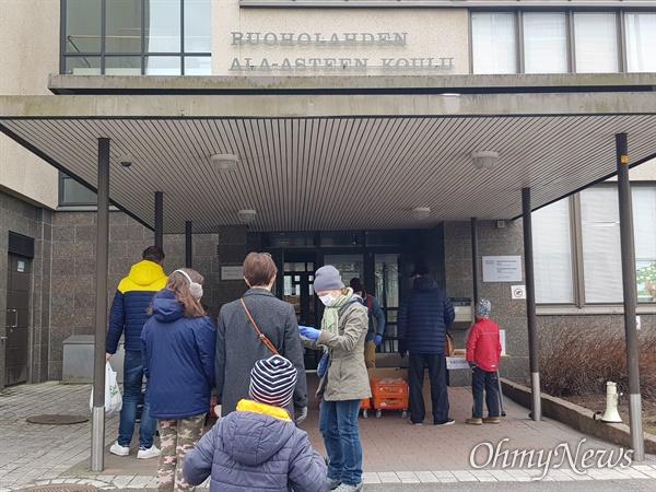 핀란드 헬싱키의 한 초등학교의 급식 배급 모습. 집으로 가져갈 급식을 배분하기 전 명단에서 학생의 이름과 학교를 확인하고 있다.