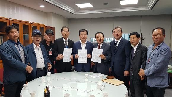 2018년 10월 강석진 의원과 거창,산청,함양사건 유족들이 합의서를 보이고 있다.