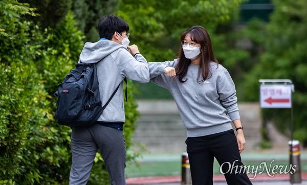 코로나19로 인해 개학 연기 후 고3의 첫 등교일인 20일 오전 서울 종로구 경복 고등학교에서 고3 학생이 등교를 하며 교사와 팔꿈치 인사를 하고 있다.