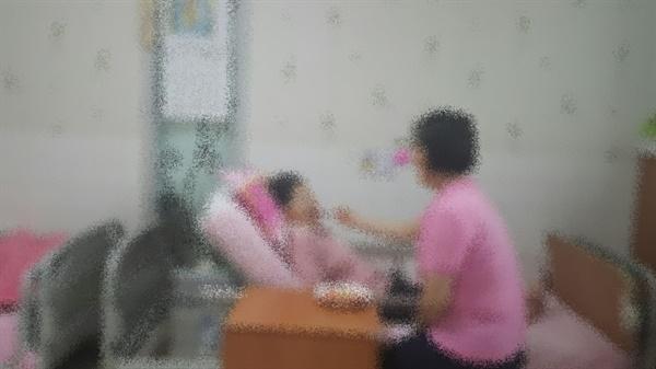 한 요양보호사가 병상에 누워있는 환자를 돌보고 있다.