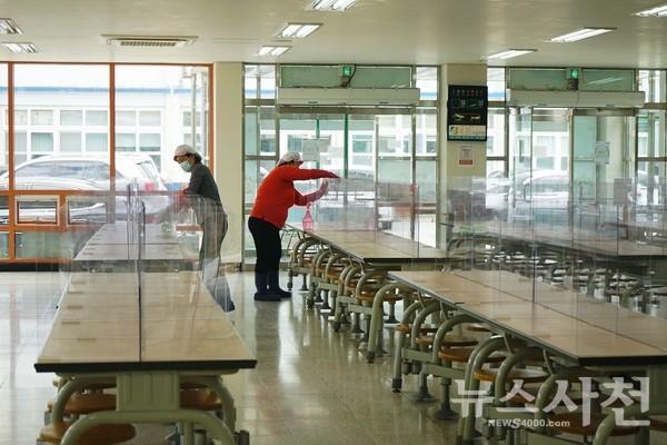 고3 학생들의 점심시간이 끝나고, 급식소에 설치된 투명칸막이를 소독하고 있다.
