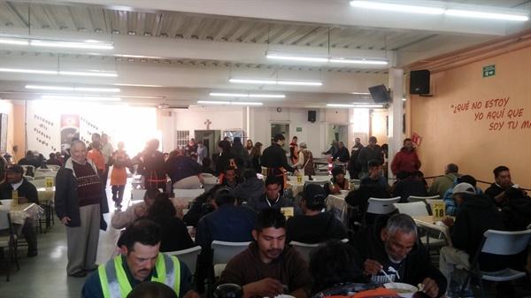 식당 내부에서 식사를 하는 모습. 중앙 통로에 서 있는 사람이 신부님이시다. 주황색 앞치마를 한 사람들은 자원봉사자들이다.