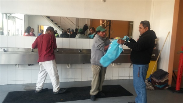 식당 입구 세면대에서 손을 씻은 이들에게 자원봉사자가 마른 수건을 제공해주고 있다.