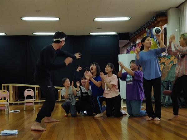 어린 여공 역할을 맡은 순회 지역의 어린이들과 연습하는 배우들