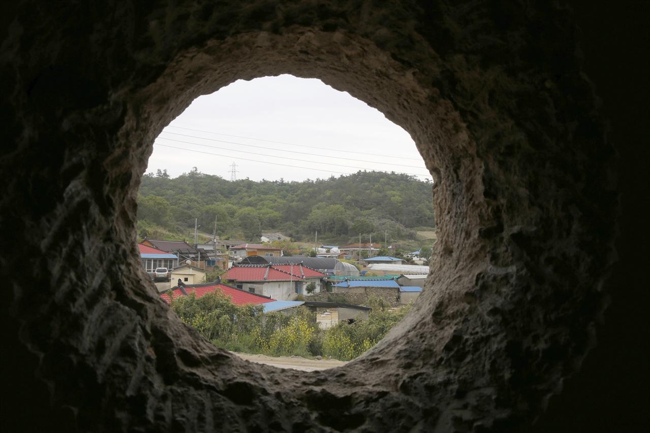 맷돌의 밑바닥을 깎아서 둥근 창틀로 만든 창, 그 둥근 창으로 마을이 보인다. 전라남도 신안군 증도면 대기점도 북촌마을에 있는 안드레아의 집이다.