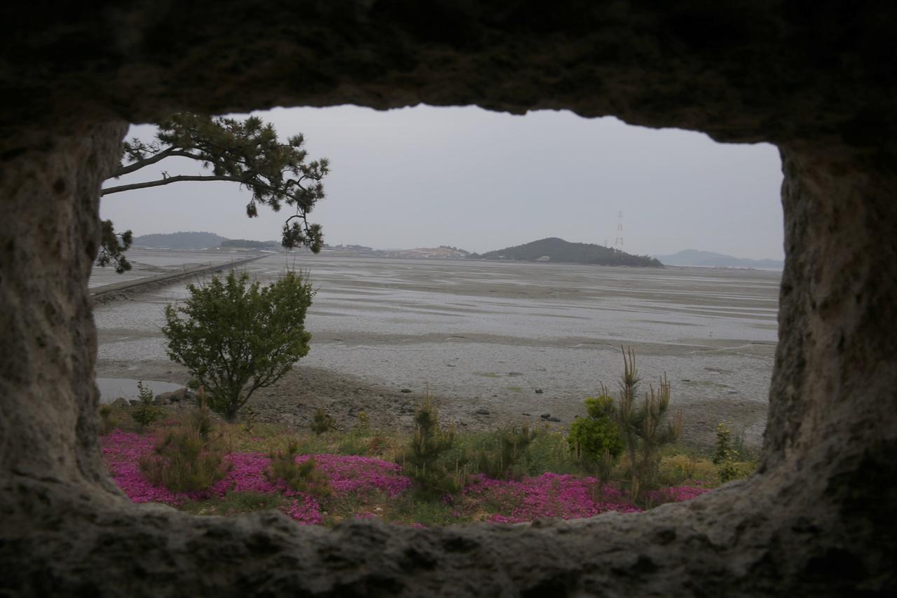 직사각의 창으로 노두와 바다 건너편의 섬이 보인다. 돼지의 먹이를 담아주는 콘크리트 구유를 깎아서 창틀로 만들었다. 신안군 증도면 대기점도의 안드레아의 집 풍경이다.