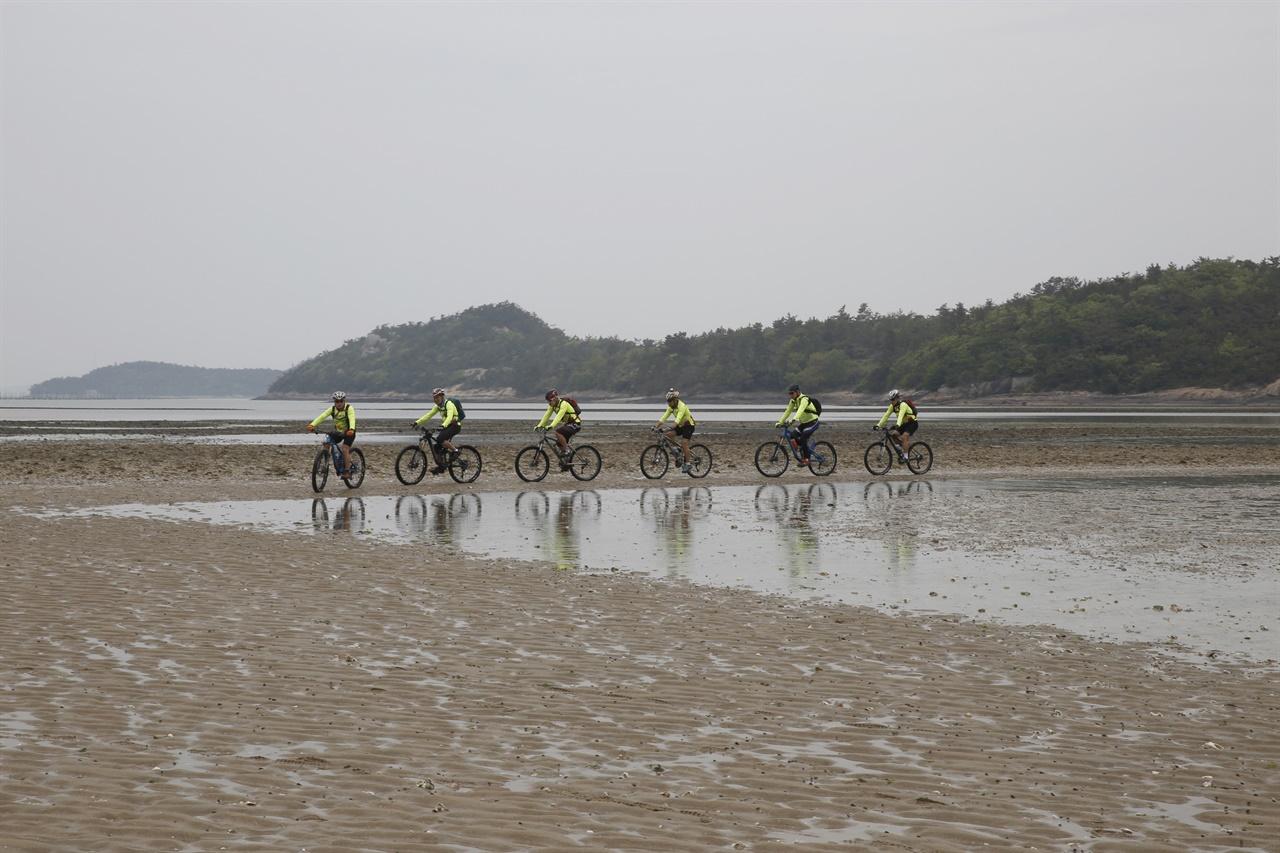 섬의 해변에서 자전거를 타며 여행을 하고 있는 동호인들. 바닷물에 비치는 두 바퀴가 환상경을 연출하고 있다. 바닷물이 빠진 신안 기점소악도의 진섬과 딴섬 사이 풍경이다.