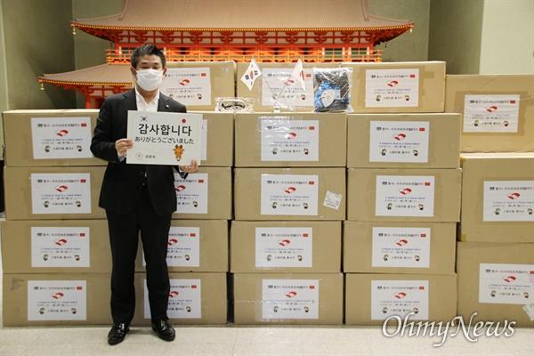 경북 경주시가 방역물품을 일본의 나라시와 교토시에 전달한 가운데 물품을 받은 나라시 나ㅏ가와 겐 시장이 '감사합니다'란 팻말을 들고 있다.