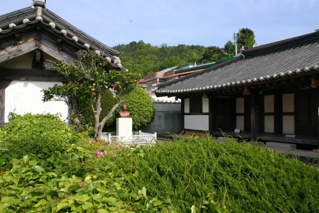 담 밖에서 바라본 생가 안채, 마당 한구석에는 김영삼 흉상이 세워져 있다.