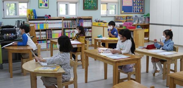 6일 경남 김해 관동초등학교에서 1학년 학생들이 마스크를 낀 채 거리를 두고 앉아 돌봄교실 수업을 듣고 있다. 2020.5.6