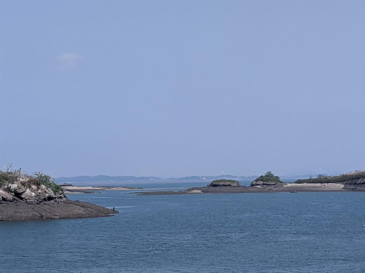 전도에서 오가도를 바라보며 낚싯줄을 내리고 있는 모습 모자 모양의 섬인 전도 아랫쪽의 까만 점이 낚시꾼이고 오른쪽 끝 일부 모습이 나타난 섬이 오가도이다.